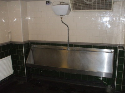 Large stainless steel urinal in a London pub.