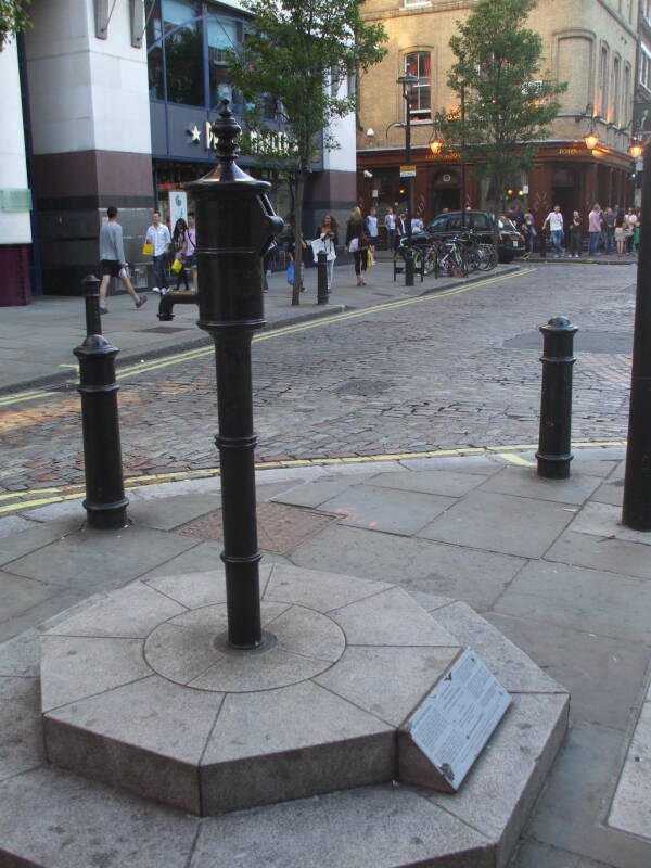 The famous water pump found to be the focus of the 1854 cholera epidemic in London.  Narrow street, Sir John Snow pub in the background.