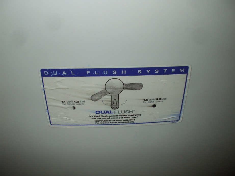 Sticker explaining a dual-flush toilet handle on the tank.