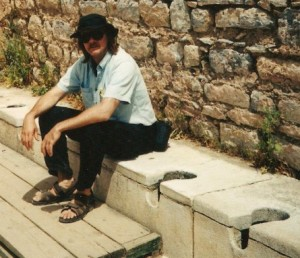 Bob Cromwell seated on the ancient public toilets in Ephesus.