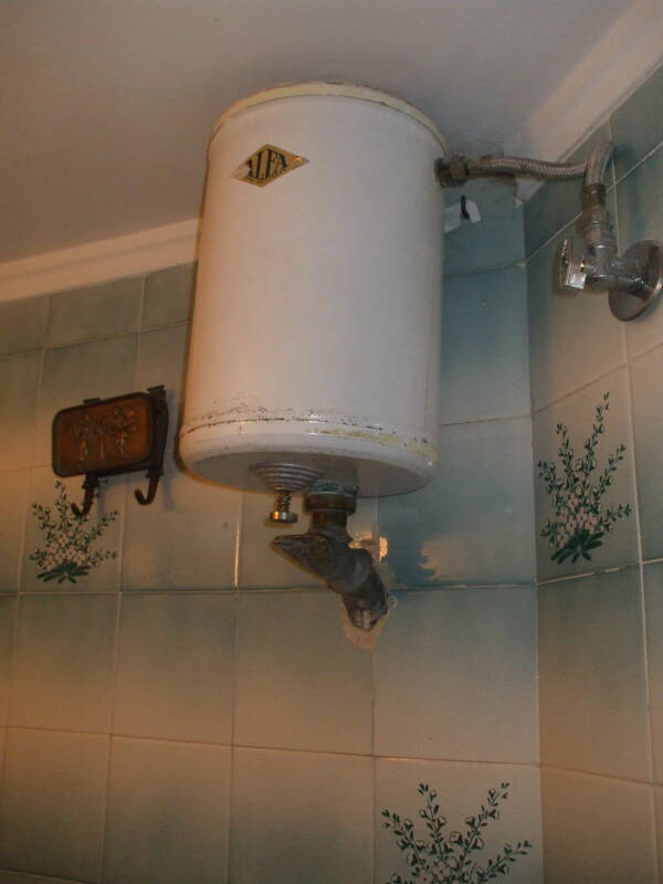 Toilet flush tank mounted near the ceiling.