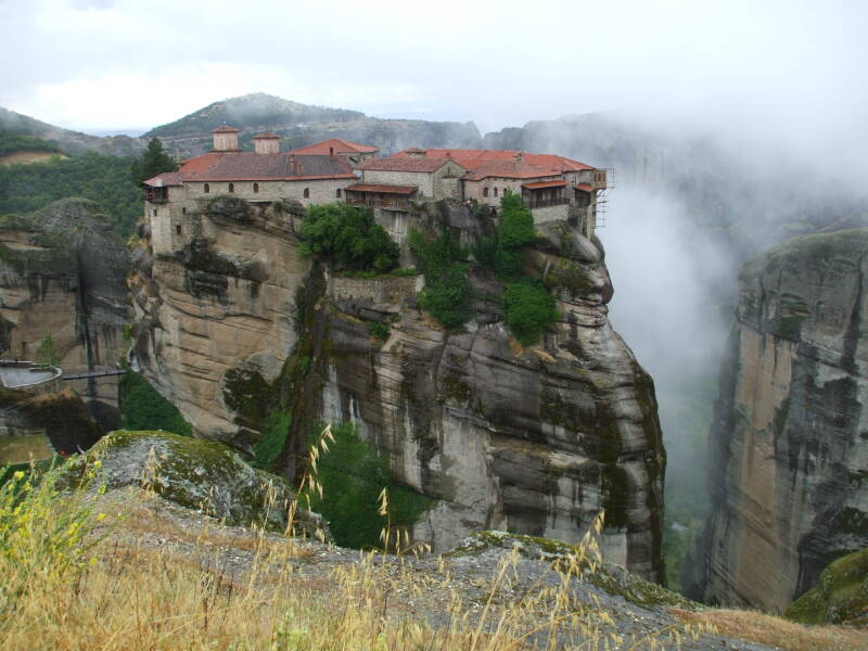 The monastery of Moni Varlaam at Meteora, on a tall rock pillar with cliff faces and clouds in the background.