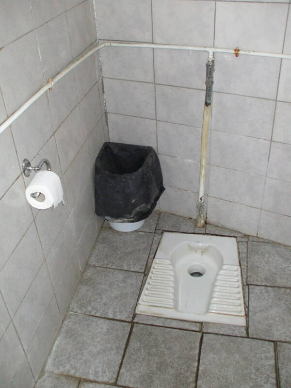 Greek squat toilet in a monastery at Meteora, with toilet paper roll, waste bin, and visible plumbing.