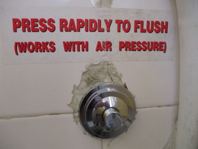 'Press rapidly to flush (works with air pressure)' -- Sign above a typical Greek toilet in the Students' and Travelers' Inn, in Athens.