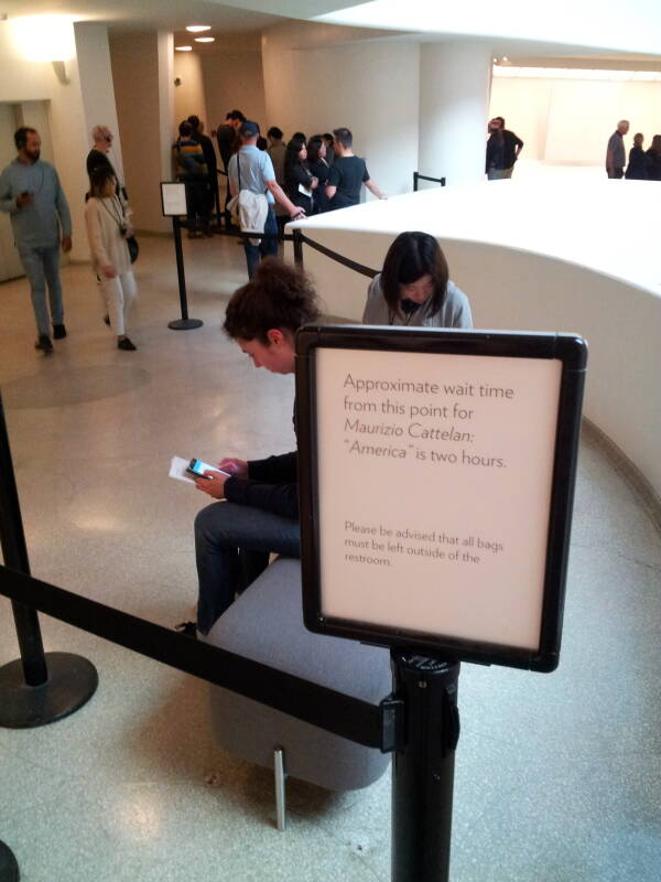 Sign for the waiting line to use the solid gold toilet 'America' Fluxus artwork at the Guggenheim Museum in New York.
