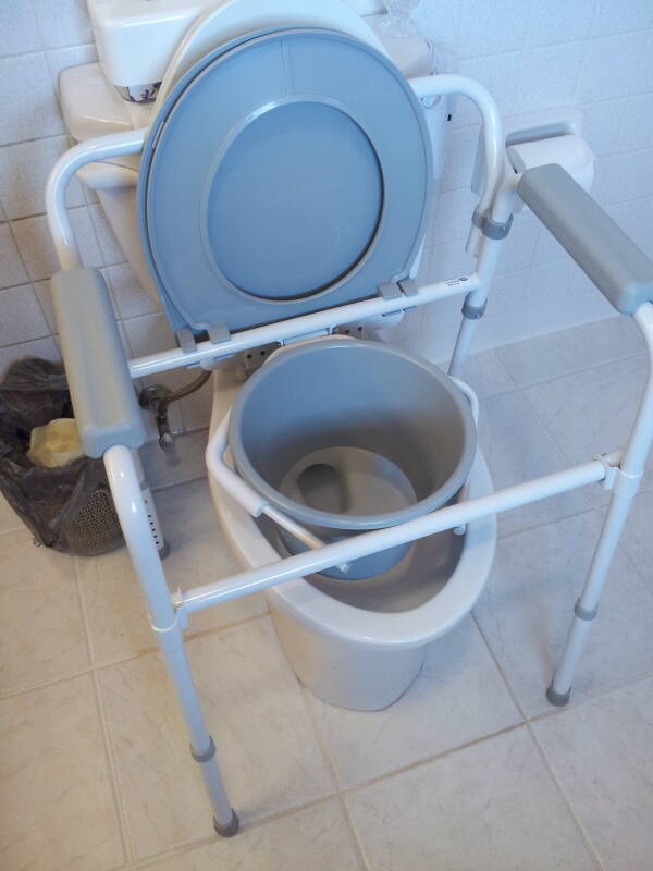 'Three-in-one' portable toilet unit placed over toilet.