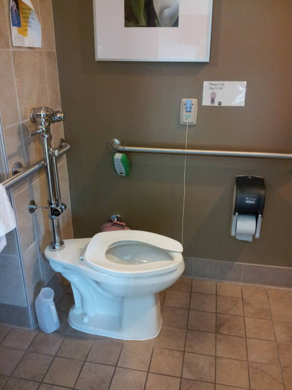 Hospital toilet with bedpan cleaning attachment, handrails, and call cord.