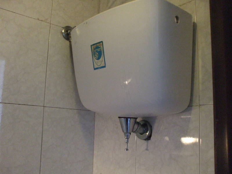 Wall-mounted toilet flush tank in Italy.