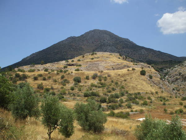 Ancient Mycenae, its hilltop in sunlight, the mountain behind is shadowed by cloud.