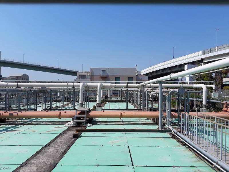 Covered sedimentation and aeration tanks and overhead pipes at the Ebie Sewage Treatment Plant in Osaka.