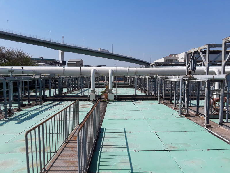 Covered sedimentation and aeration tanks and overhead pipes at the Ebie Sewage Treatment Plant in Osaka, curving overhead highway in the background.