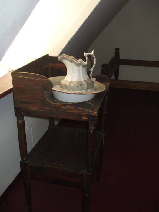 Washbasin in Edgar Allan Poe's bedroom in Baltimore.  Ceramic bowl and pitcher in a wooden stand with a large hole.