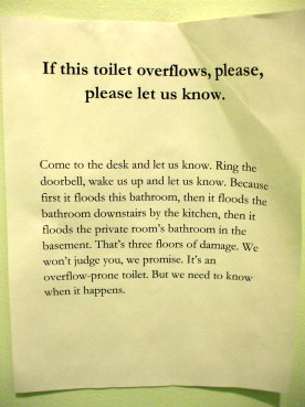 Warning sign about a flooding toilet.