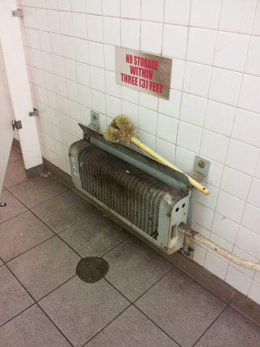 Radiator and large scrub brush in the Delancey Street — Essex Street station of the New York City MTA subway system in Manhattan.